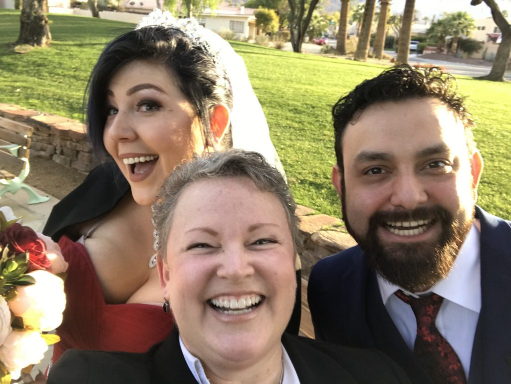 A couple and their officiant selfie memory.
